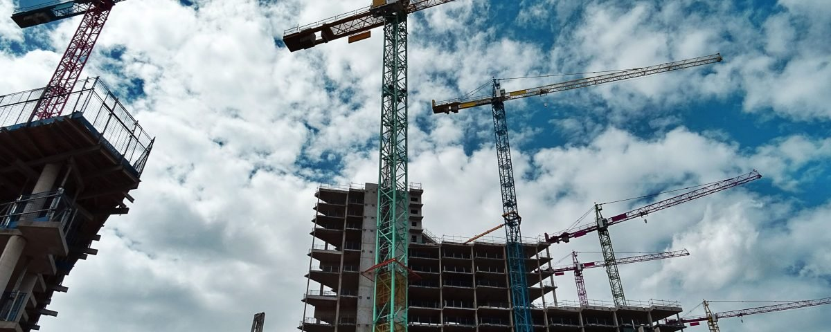 Construction site, with 3 cranes erecting a building